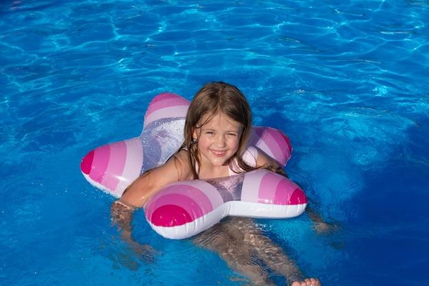 Счастливая улыбающаяся маленькая блондинка в очках плавает в бассейне в шляпе санта-клауса