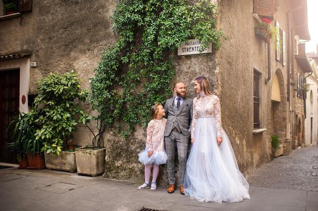 Счастливая стильная семья стоит в старом городе сирмионе в италии.