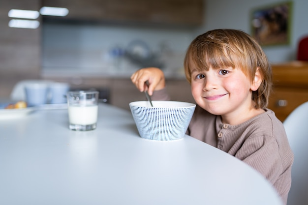 잠옷을 입은 행복한 어린 소년이 학교 시작 전 아침에 집에서 아침을 먹고 있습니다. 어린이를 위한 건강식.