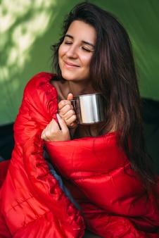 幸せな観光客の女性がテントに座ってお茶を飲んでいます。テントでのキャンプ-キャンプ中の少女。寝袋に入れて、熱いお茶を飲む女性観光客。キャンプ場での朝。ポートレート