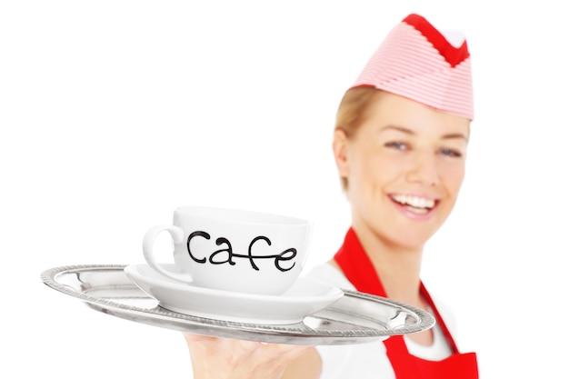 Счастливая официантка позирует с подносом и кофе на белом фоне