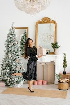 幸せな女性は彼女の手でクリスマスプレゼントを持って、クリスマスツリーでそれを開きます