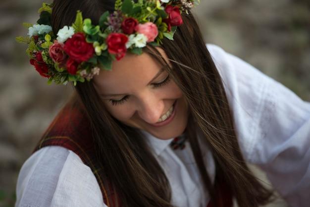 Счастливая женщина в латышском народном костюме с цветочной короной на голове смотрит вниз, празднование летних праздников (лиго) в латвии.