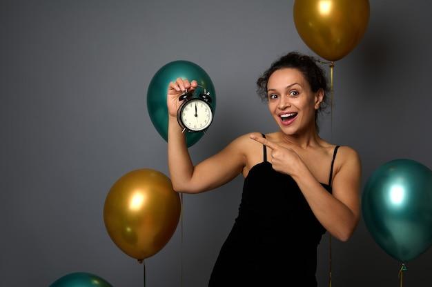 이브닝 드레스를 입은 행복한 여성은 파티에서 기뻐하고 손에 든 알람 시계의 시간을 보여줍니다. 자정입니다. 크리스마스, 새해, 복사 공간이 있는 회색 배경의 생일 개념 축하