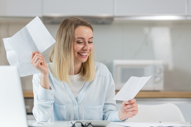 행복한 여자가 대출을 종료하기 위해 은행의 문서를 검토하고 있습니다.