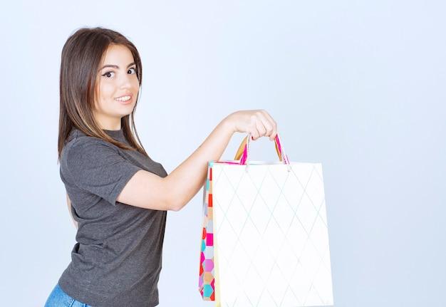 白い背景の上の買い物袋をたくさん持っている幸せな女性モデル。