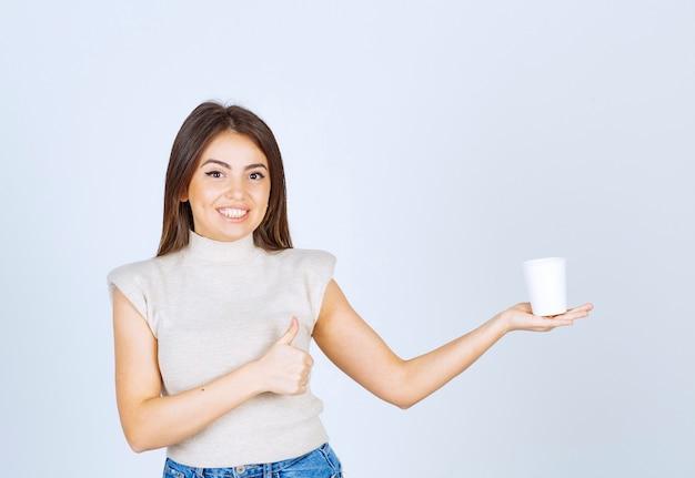 Модель счастливая женщина держит пластиковый стаканчик и показывает палец вверх.