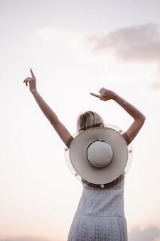 행복한 여자가 하늘을 배경으로 포즈를 취하고 있는 아름다운 젊은 금발의 사진에 손을 들고 ...