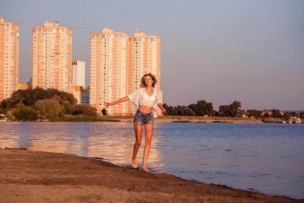 幸せな女性がビーチに沿って自由に走り、白いシャツとデニムのショーで笑顔の美しいブロンド...