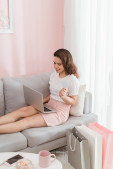 Счастливая женщина делает покупки в интернете с помощью кредитной карты из своего современного дома, сидя на диване с ноутбуком.