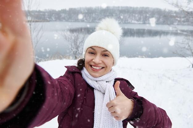 Счастливая женщина показывает палец вверх и улыбается в камеру, делая селфи, наслаждаясь падающим снегом