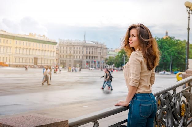 Счастливая женщина гуляет по историческим улицам санкт-петербурга в центре города