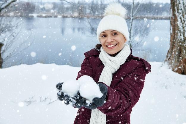 白いニットのウールの帽子とスカーフを身に着けている幸せな女性は笑顔で雪玉を手に持っています