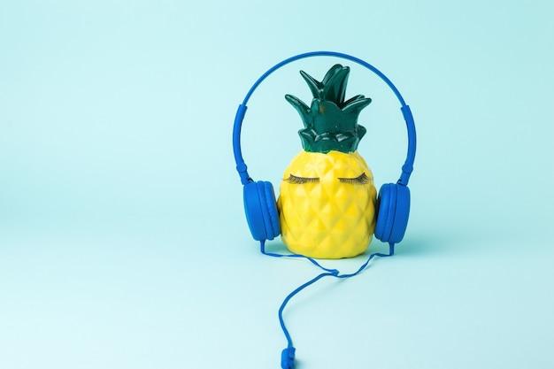 青い背景に青いヘッドフォンで幸せな黄色のパイナップル。音楽への愛。