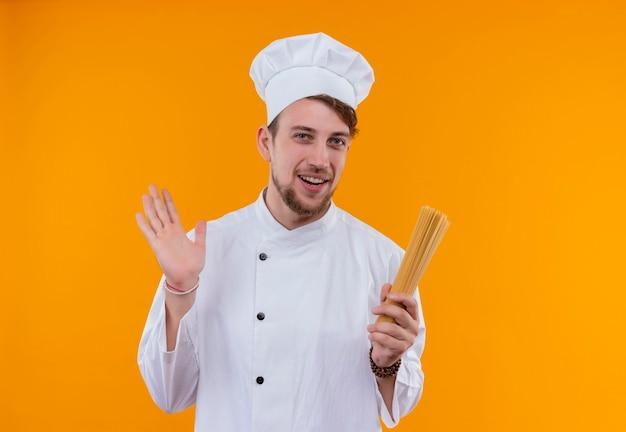 オレンジ色の壁にスパゲッティを保持している白い制服を着た幸せな若いひげを生やしたシェフの男