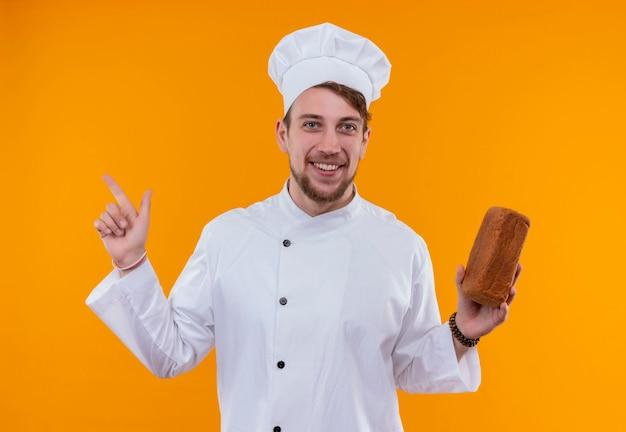 オレンジ色の壁にパンの塊を保持しながら人差し指で上向きの白い制服を着た幸せな若いひげを生やしたシェフの男