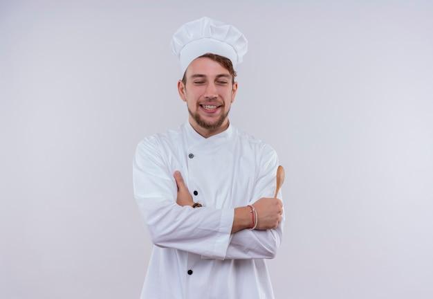 白い壁に立っている間、白い炊飯器の制服と目を閉じて木のスプーンを保持している帽子を身に着けている幸せな若いひげを生やしたシェフの男
