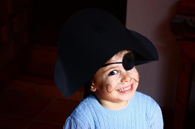 Счастливый мальчик в костюме пирата. черный фон.