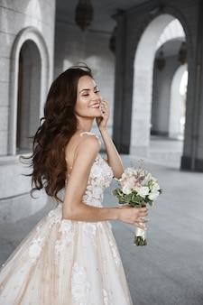 Счастливая молодая невеста со свадебной прической в белом кружеве во дворе старинной церкви в б ...