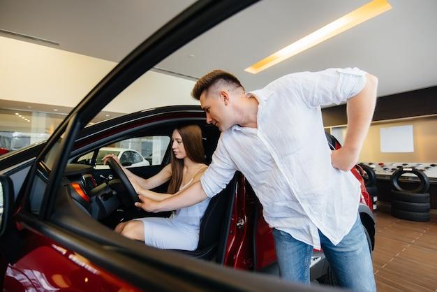 Счастливая молодая пара выбирает и покупает новую машину в автосалоне. покупка новой машины.