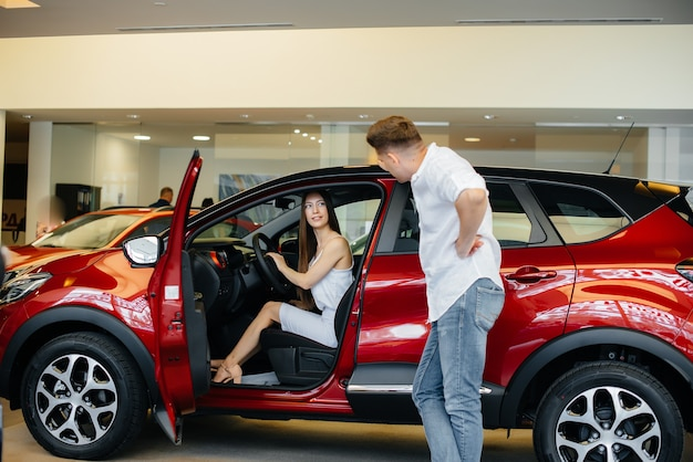 Счастливая молодая пара выбирает и покупает новую машину в автосалоне
