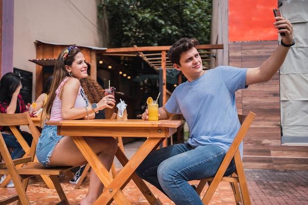 スマートフォンで自分撮りをしている幸せな若いカップル-バーの外に座って、ジュースを飲んでいる若い笑顔のカップル。