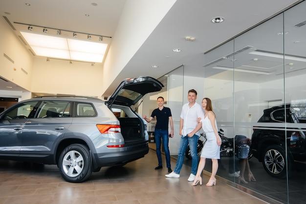 Счастливая молодая семья выбирает и покупает новую машину в автосалоне. покупка новой машины.