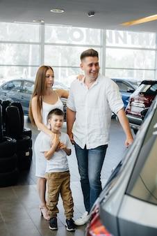 행복한 젊은 가족이 자동차 대리점에서 새 차를 선택하고 구입합니다. 새 차를 사는 것.