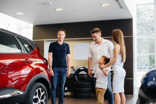 幸せな若い家族は、自動車販売店で新しい車を選んで購入します。新しい車を買う。