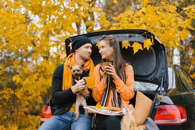 秋の森で屋外で過ごした一日の後、幸せな若い家族がリラックスしています