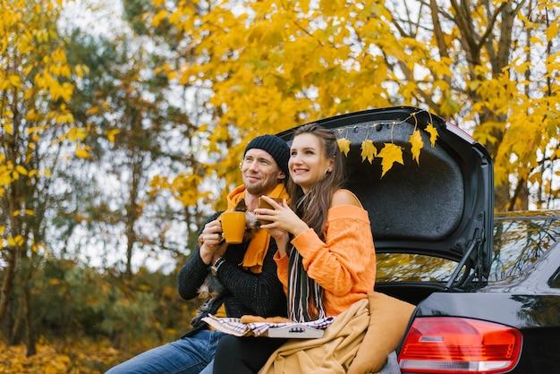 秋の森で屋外で一日を過ごした後、幸せな若い家族がリラックスしています。