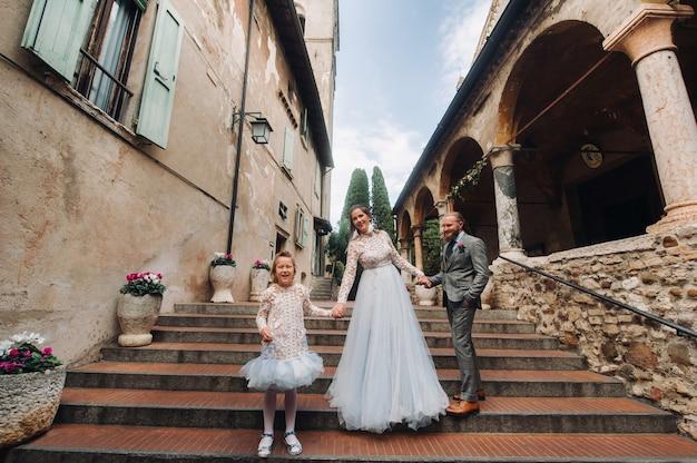 Счастливая молодая семья гуляет по старому городу сирмионе в италии. стильная семья в италии гуляет.
