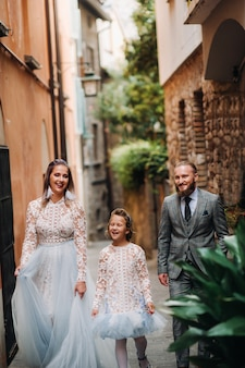 幸せな若い家族がイタリアのシルミオーネの旧市街を歩きます。散歩でイタリアのスタイリッシュな家族。