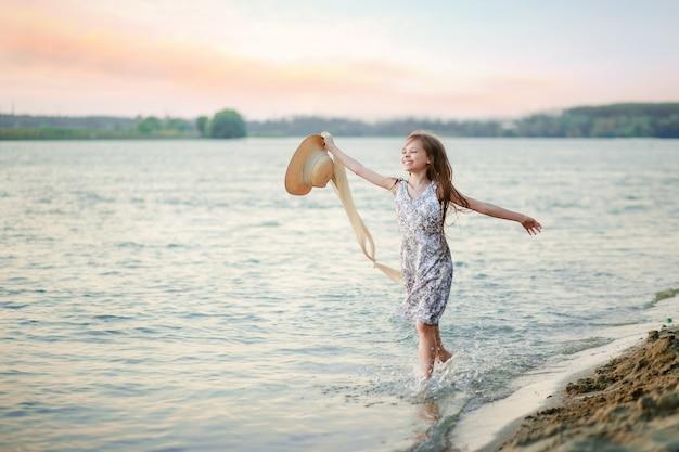 幸せな少女が水上を岸に沿って走り、帽子を振る。女の子は川から水をはねて、夏の始まりに満足しています