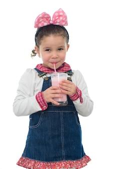 白で隔離されるいちごのミルクセーキと幸せな若い女の子