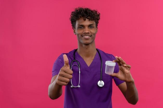 プラスチック製の標本瓶を押しながら親指を現して聴診器で紫の制服を着た巻き毛の幸せな若いハンサムな浅黒い医者