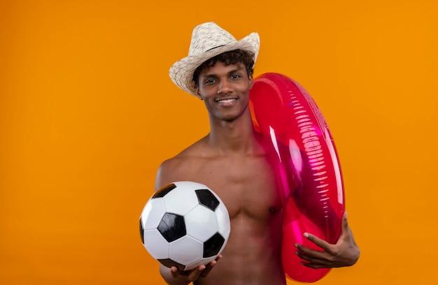 インフレータブルプールリングとボールを保持している太陽の帽子をかぶっている巻き毛を持つ幸せな若いハンサムな浅黒い男