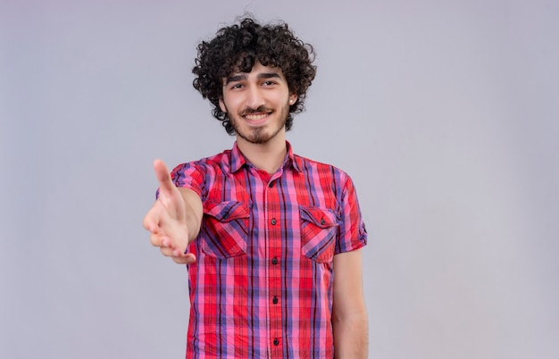 Счастливый молодой красавец с вьющимися волосами в клетчатой рубашке зовет ближе жестом руки