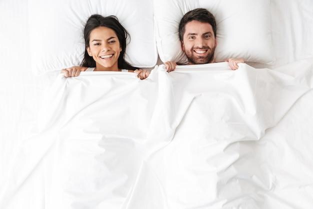 幸せな若い愛情のあるカップルは、毛布の下で覆っているベッドの皮に横たわっています