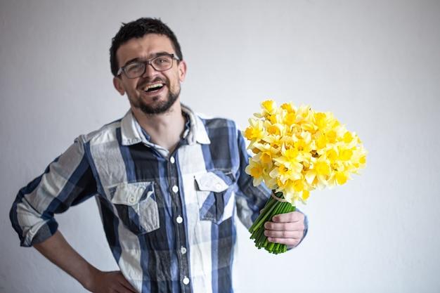 眼鏡と水仙の花束とシャツを着た幸せな若い男。挨拶と女性の日の概念。