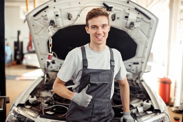 Счастливый молодой человек за работой. автосервис и ремонт.