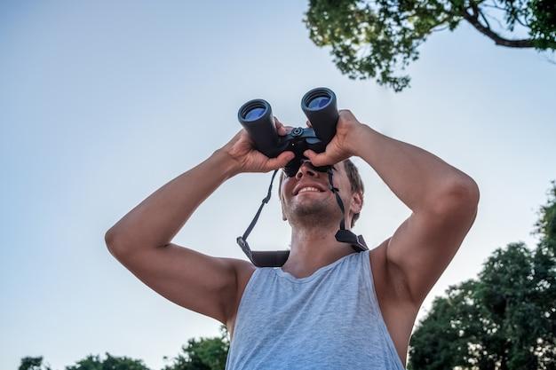 空と植生を背景に立って、双眼鏡で遠くを見つめる幸せな青年。