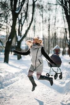 幸せな若い母親がジャンプし、ベビーカーと赤ちゃんと一緒にウィンターパークを歩く