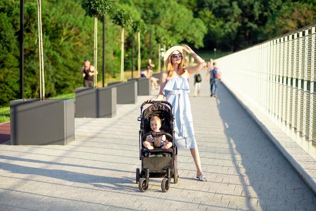 행복한 젊은 어머니는 여름에 공원에서 유모차를 타고 아기와 함께 지는 태양 아래서 즐거운 시간을 보내면서 미소를 짓습니다.