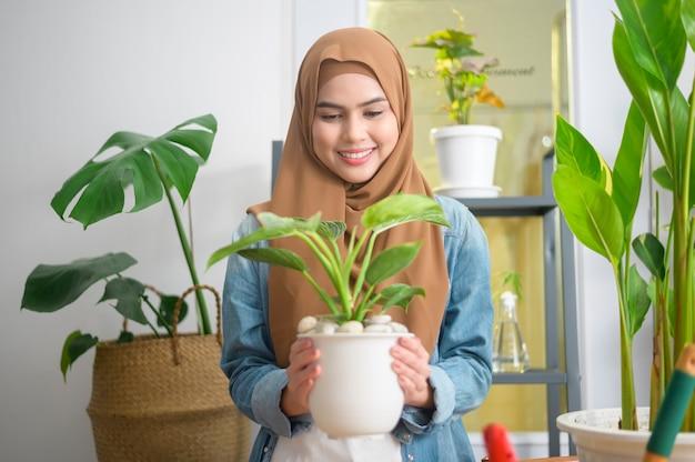 Счастливая молодая мусульманская женщина, наслаждающаяся и расслабляющая досуг в саду дома