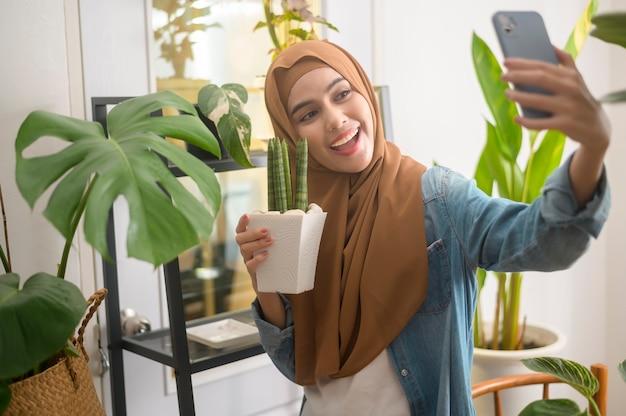 그녀의 식물과 함께 셀카를 복용하고 집에서 화상 통화를하는 행복 젊은 무슬림 여성