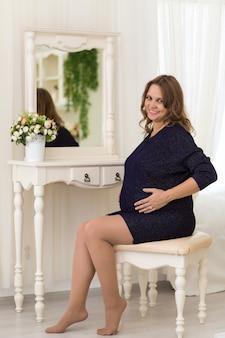 Счастливая молодая беременная женщина сидит за туалетным столиком напротив зеркала