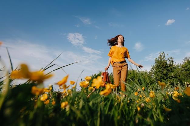 행복한 어린 날씬한 소녀가 노란 꽃 야생화 알레르기가 없는 개념의 손가락 향기를 들이마시며 들판 바닥을 가로질러 달리고 있습니다