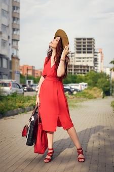 広い帽子をかぶって、幸せな若い女性は、夏に都市公園でポーズをとる