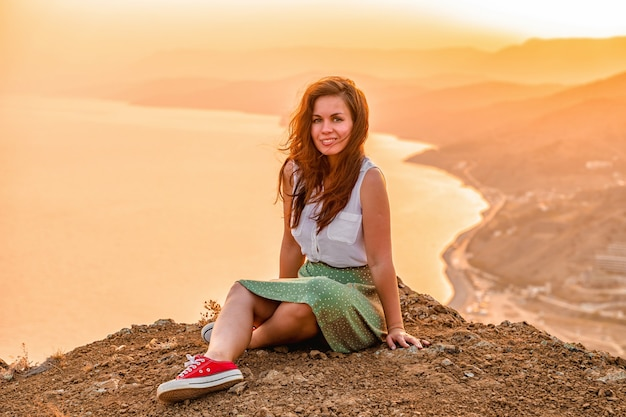 スカートをはいた幸せな若い女性は、夕日の空の下の山の崖の上に座っています